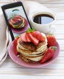 Smartphone geschotene voedselfoto - pannekoeken voor ontbijt met aardbeien Stock Afbeeldingen