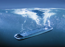 Smartphone geworfen in Wasser Stockfotografie