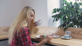 Smartphone girl using app on phone drinking coffee smiling in cafe stock video