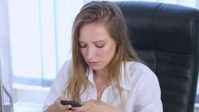 Smartphone girl using app on phone drinking coffee smiling in office. Beautiful multicultural young casual female stock video footage