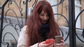 Smartphone girl using app on phone drinking coffee smiling outdoors in the city. stock footage