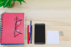 Smartphone, glasses, notebooks, pen, pencil, paper clips, green leaves pot on vintage wooden table Stock Photo