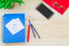 Smartphone, glasses, notebooks, pen, pencil, paper clips, green leaves pot on vintage wooden table Royalty Free Stock Image