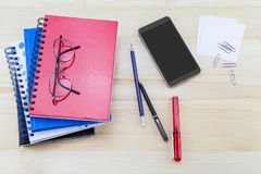 Smartphone, glasses, notebooks, pen, pencil, paper clips on vint Royalty Free Stock Images
