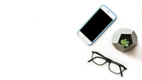 Smartphone, glasses, office plant top view  flat lay composition with free copy space on the left side. Flat lay composition with free copy space Stock Images