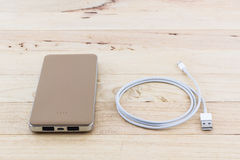 Smartphone with golden power bank. Royalty Free Stock Photography