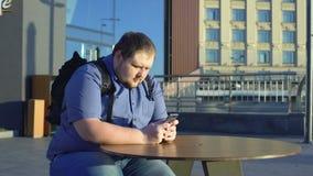 Smartphone gordo do desdobramento do homem novo, assento no café exterior, estilo de vida preguiçoso video estoque
