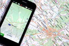 Smartphone with GPS and a map. Smartphone with GPS function and a paper map stock images