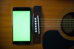 Smartphone-Grünschirm auf einer Akustikgitarre Stockbilder