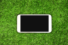 Smartphone on grass Royalty Free Stock Image