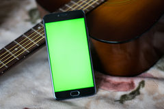 Smartphone with green screen on an acoustic guitar Royalty Free Stock Images