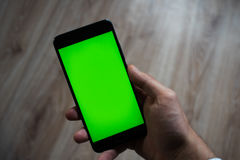 Smartphone with green screen for key chroma screen. In the hands of a man Stock Photos