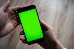 Smartphone with green screen for key chroma screen. In the hands of a man Stock Images