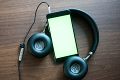 Smartphone with green screen for key chroma screen. Headphones, smartphone with green screen for key chroma screen.  On the table Stock Images