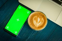 Smartphone with green screen near coffee and laptop