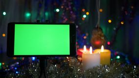 Smartphone with a green screen. On a New Year`s background, flashing garlands, burning candles. stock footage