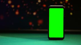 Smartphone with green screen on poker table, lights sparkling on background stock video