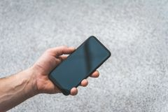 Smartphone in hand, on the background of concrete tiles. royalty free stock photography