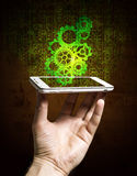 Smartphone in hand on the background of the mechanism of gears Royalty Free Stock Photography