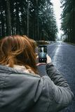 Smartphone in hand on the background winter road in the woods royalty free stock photos