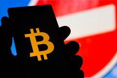 Smartphone in hand with Bitcoin cryptocurrency logo. Prohibiting. Red sign on background. Banned money concept. Censorship. Instant transactions block. Danger Stock Photography