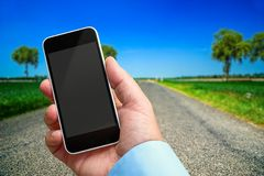 Smartphone in hand with a blank area to insert a custom image. Beautiful landscape on background. Concept of Smartphone in hand with a blank area to insert a royalty free stock images