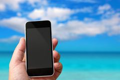 Smartphone in hand with a blank area to insert a custom image. Paradisiac sea on background. Concept of Smartphone in hand with a blank area to insert a custom royalty free stock image