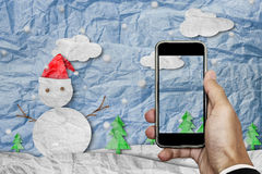 Smartphone on hand with blank screen, crumpled paper cut snowman in winter, with copy space on screen royalty free stock photos