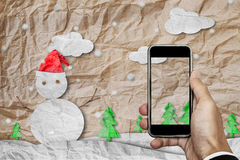 Smartphone on hand with blank screen, crumpled paper cut snowman in winter, with copy space on screen stock images