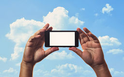 Smartphone in hand and blue sky Stock Images