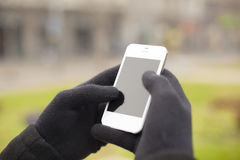 Smartphone in hand with gloves Stock Image