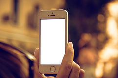 Smartphone in hand. Hand holding smartphone with white blank screen Royalty Free Stock Photo