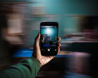 Smartphone in hand with motion blur in the background royalty free stock photo