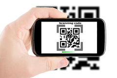 Smartphone in hand scanning code royalty free stock photography