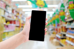 Smartphone on hand in supermarket. Background royalty free stock images