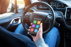 Smartphone in hands of a car driver. The display shows an smart car app with navigation Stock Photos