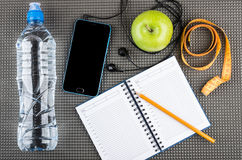 Smartphone with headphones, apple, bottle, measures tape, notepa Royalty Free Stock Photography