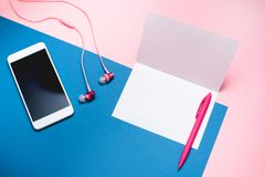 Smartphone, headphones and blank white sheet of paper. stock photos