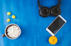 Smartphone, headphones and coffee cup on rustic wooden table. Top view stock photography