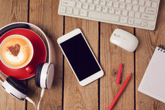 Smartphone, headphones and coffee cup on wooden table. Business workplace or workspace concept. Stock Photo