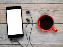 Smartphone with headphones and coffee cup on wooden table. Top view Stock Photo