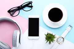 Smartphone with headphones, coffee, plant royalty free stock photo