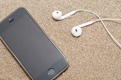 Smartphone with headphones on sea sand. Royalty Free Stock Photography