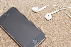 Smartphone with headphones on sea sand. Royalty Free Stock Image