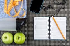 Smartphone with headphones, towel, apples, plastic shaker, notep Stock Image