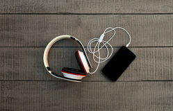 Smartphone and headphones on a wooden background. Listen to musi Stock Photography