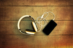 Smartphone and headphones on a wooden background. Listen to musi Stock Photos