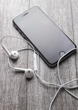 Smartphone and headphones on the wooden table Stock Photo