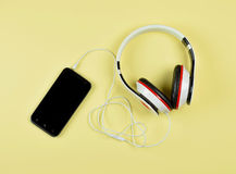 Smartphone and headphones on a yellow background. Stock Photos