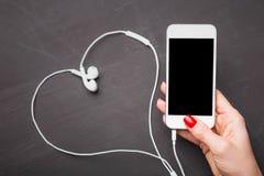 Smartphone with heart shape headphones Stock Image